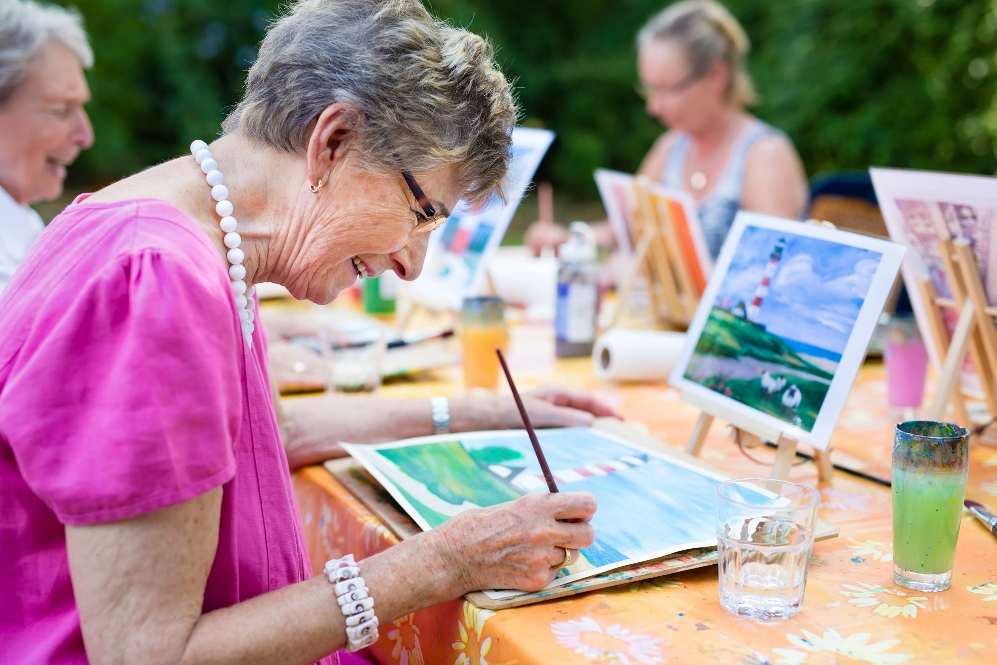 A group of seniors enjoy a community painting class and spend time socializing